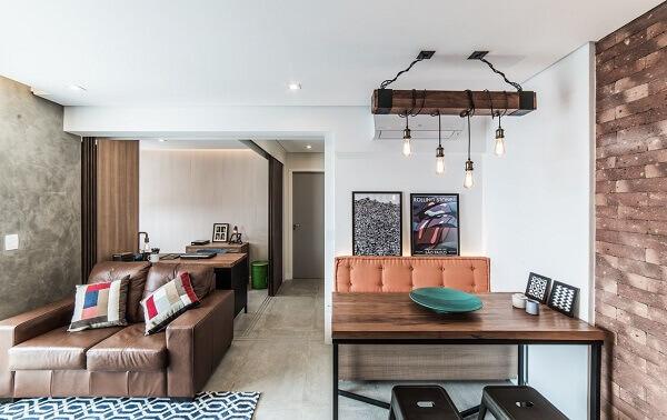 Marrom no sofá, almofadas coloridas e quadros grandes