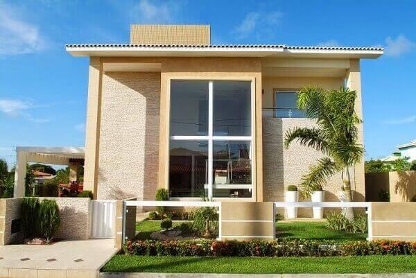 Muro de vidro e alvenaria amarela combinando com a frente da casa Foto de Decor Salteado