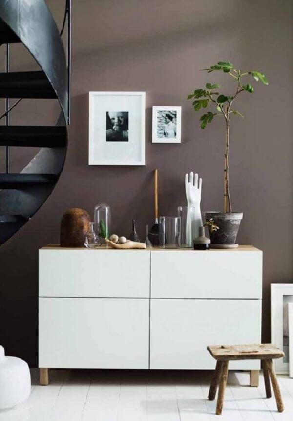 Os móveis em tom branco quebram a seriedade da parede marrom. Fonte: Pinterest