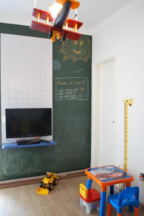 Quarto infantil com parede de lousa verde e brinquedos Projeto de Projetica Design e Arquitetura