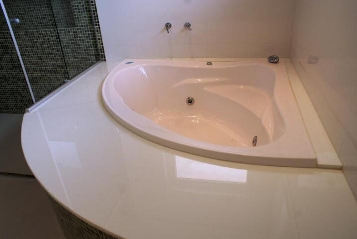 Sala de banho com banheira pequena com hidromassagem no canto Projeto de Rosani Gomes