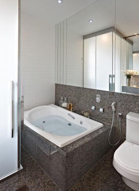 Sala de banho com parede espelhada e banheira pequena com hidromassagem branca Projeto de Gislene Lopes
