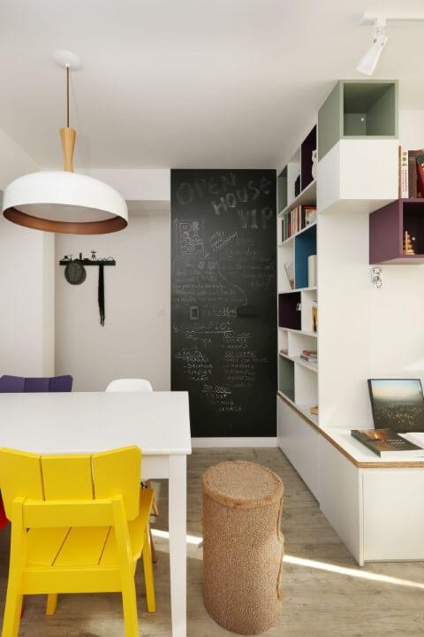Sala de estar compacta com cadeiras coloridas e painel chalkboard em parte da parede Projeto de SP Estudio