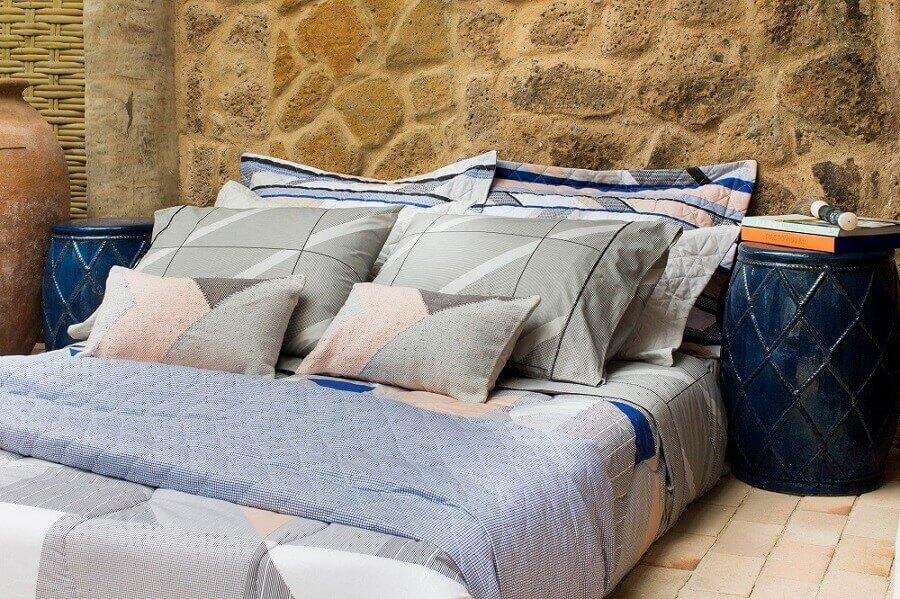 cama decorada com vários travesseiros e bonita roupa de cama