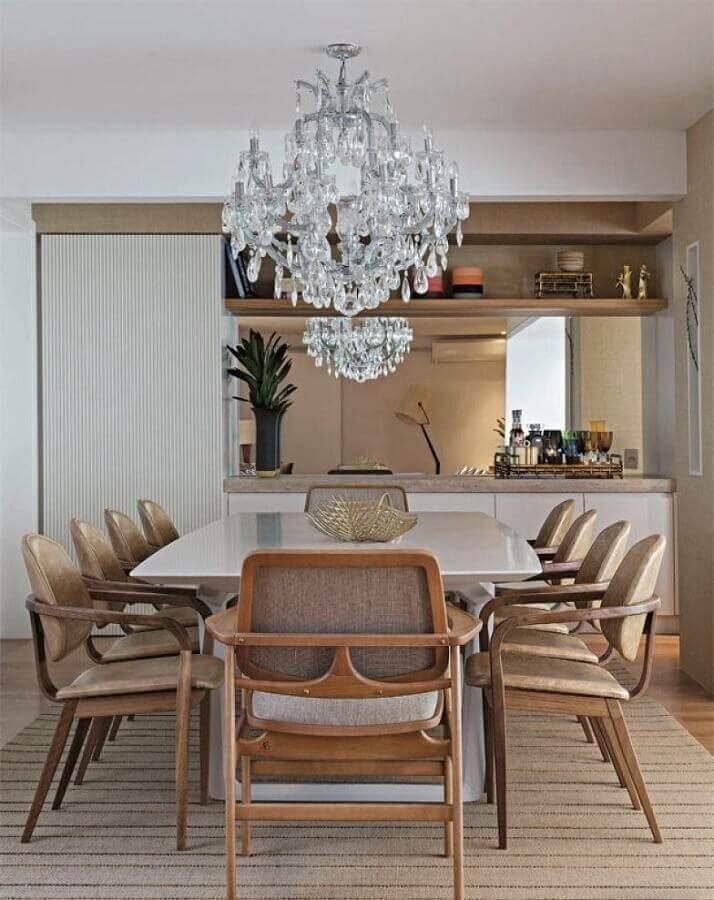 decoração com lustre de cristal para sala de jantar com mesa branca e modelo diferente de cadeira de madeira Foto Aaron Guides