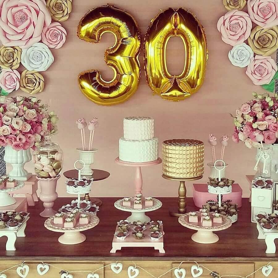 decoração de aniversário adulto em tons de rosa e dourado com painel de flores de papel Foto Aaron Guides