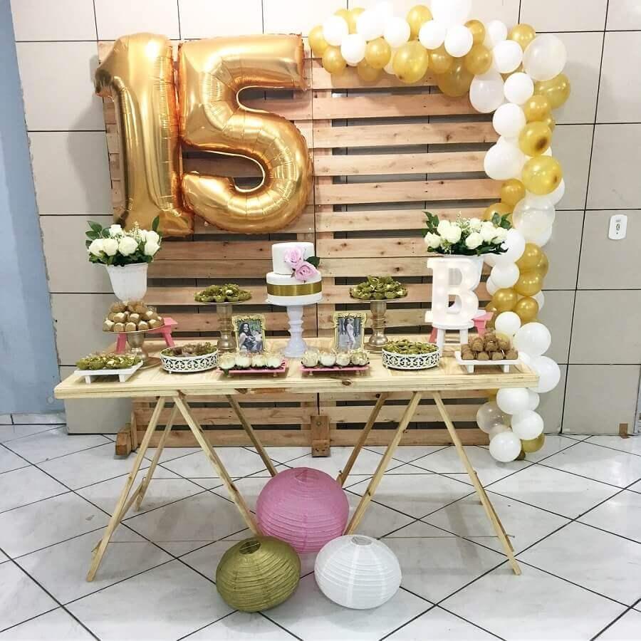 decoração de aniversário de 15 anos simples com painel de pallets e balões dourados Foto Le' Art Decor
