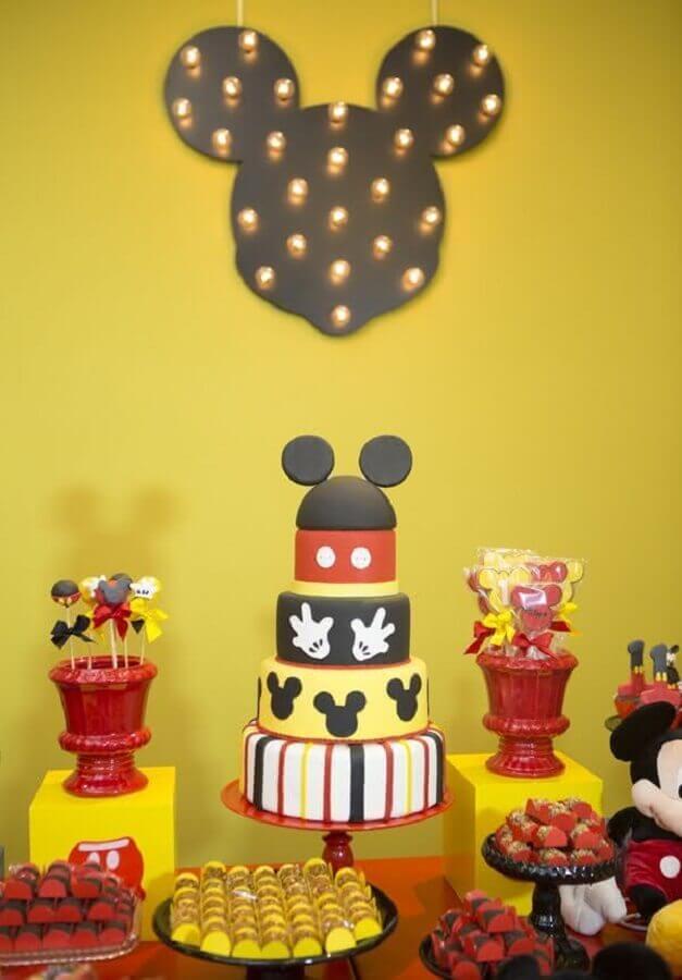 decoração de aniversário do mickey com bolo quatro andares e luminária em formato de mickey na parede Foto 321achei