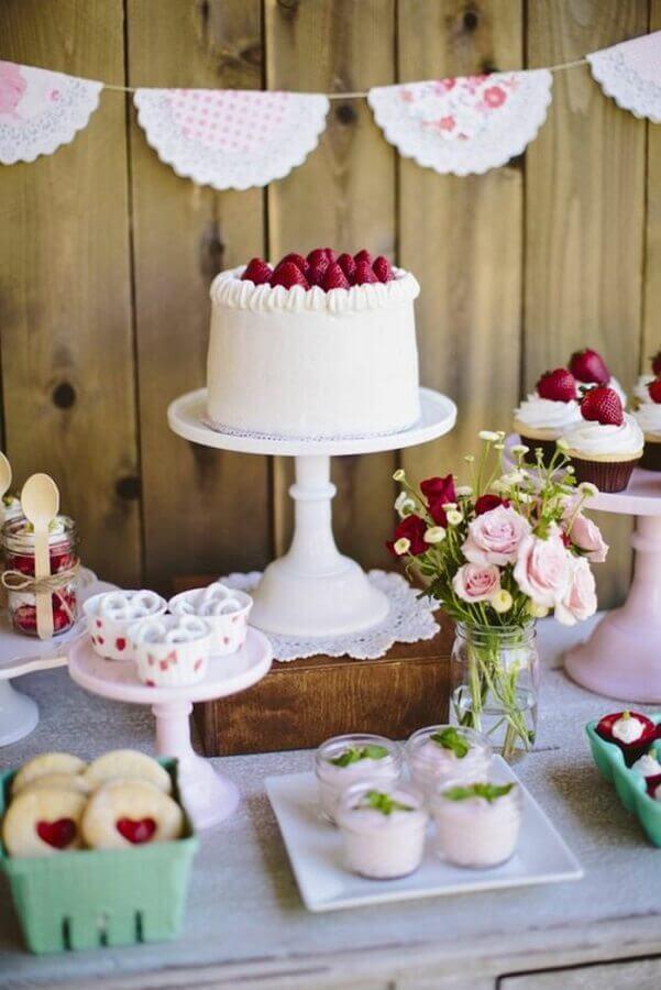 decoração de aniversário simples vermelho e branco com painel rústico e bolo de morangos Foto Archzine