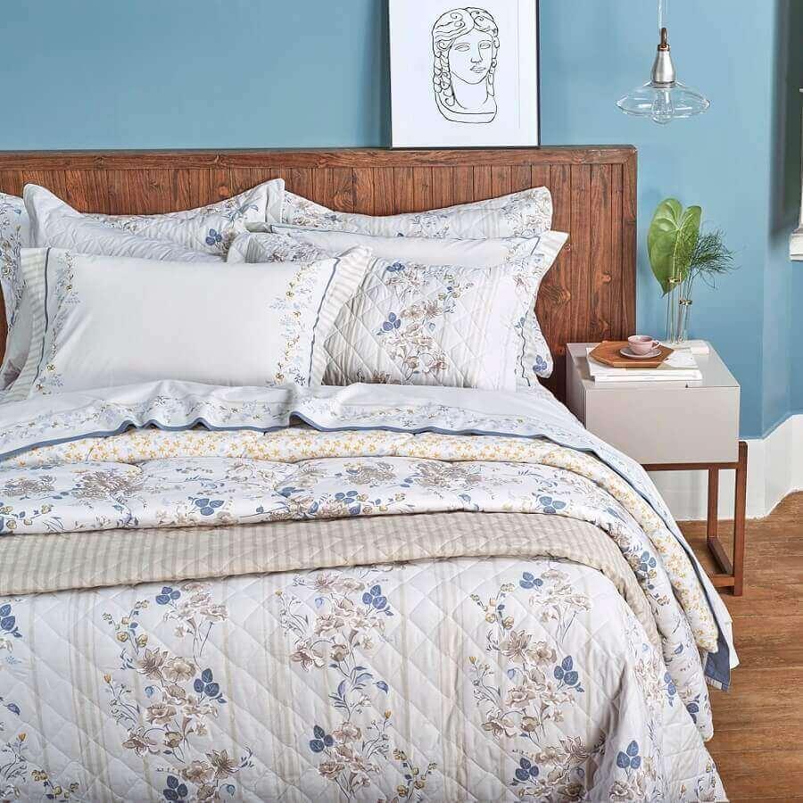 decoração de cama com cabeceira de madeira com muitos travesseiros e enxoval bonito