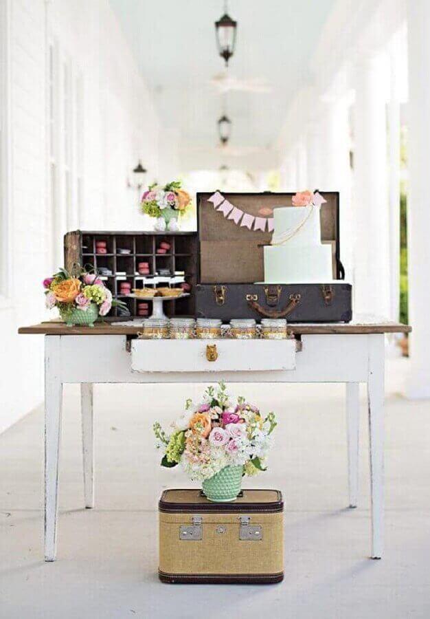 decoração de mesa de lembrancinha para noivado simples com maleta antiga e arranjos de rosas Foto Home Decoo