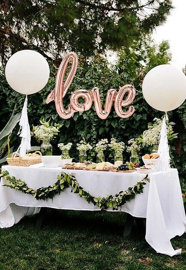 decoração de noivado simples com folhagens e balão escrito LOVE Foto Pinosy