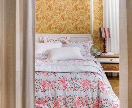 decoração de quarto com papel de parede e cama com várias camadas de enxoval