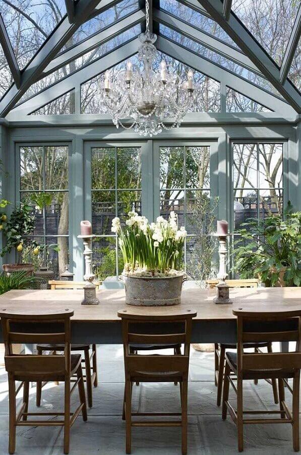 decoração de solário com mesa de madeira e lustre de cristal Foto 87Designs