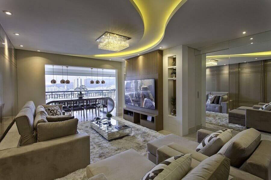 decoração em tons neutros com lustre de cristal para sala integrada com varanda Foto Iara Kilaris