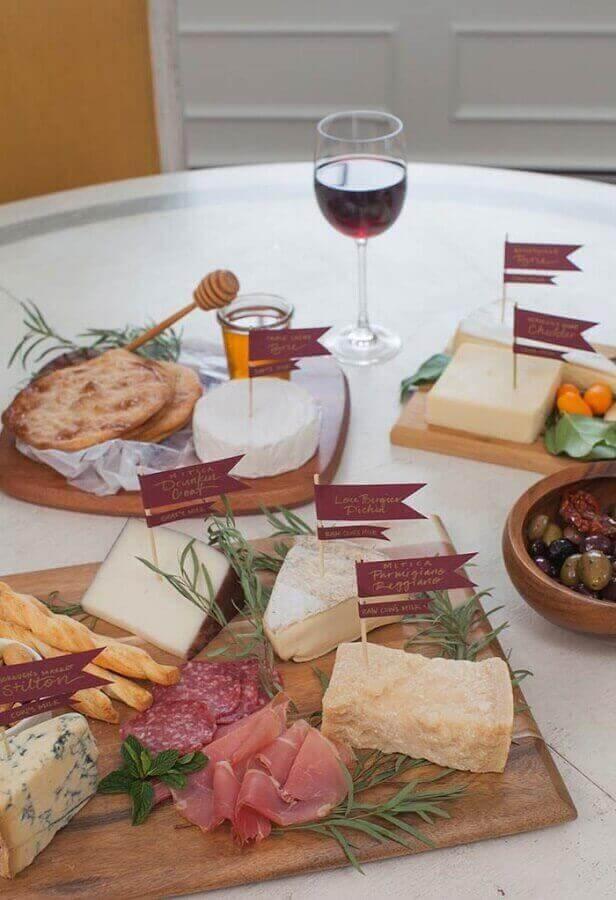 decoração para mesa de frios simples com plaquinhas sobre os queijos Foto Assetproject