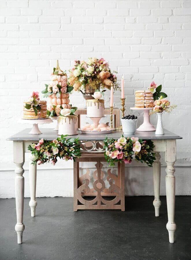 decoração para mesa de noivado simples e romântico em tons de rosa com vários arranjos de flores Foto Pesona Pengantin