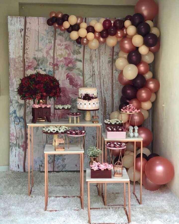 decoração simples de noivado com bolo dois andares e arranjo com balões Foto Del Bosque Decorações Locações