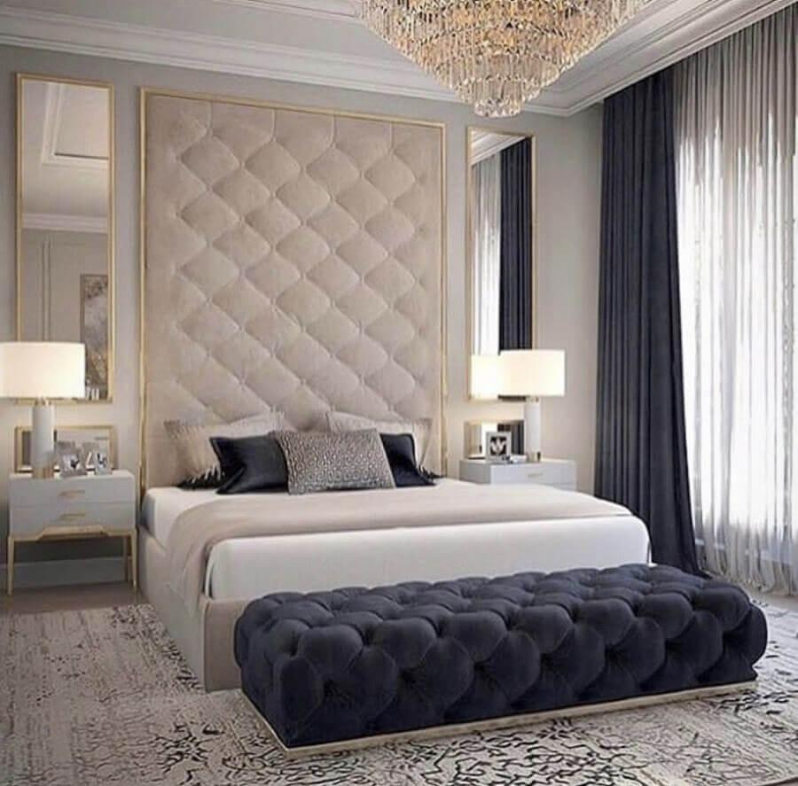 decoração sofisticada com lustre de cristal para quarto de casal com recamier azul marinho e parede estofada Foto Zozu