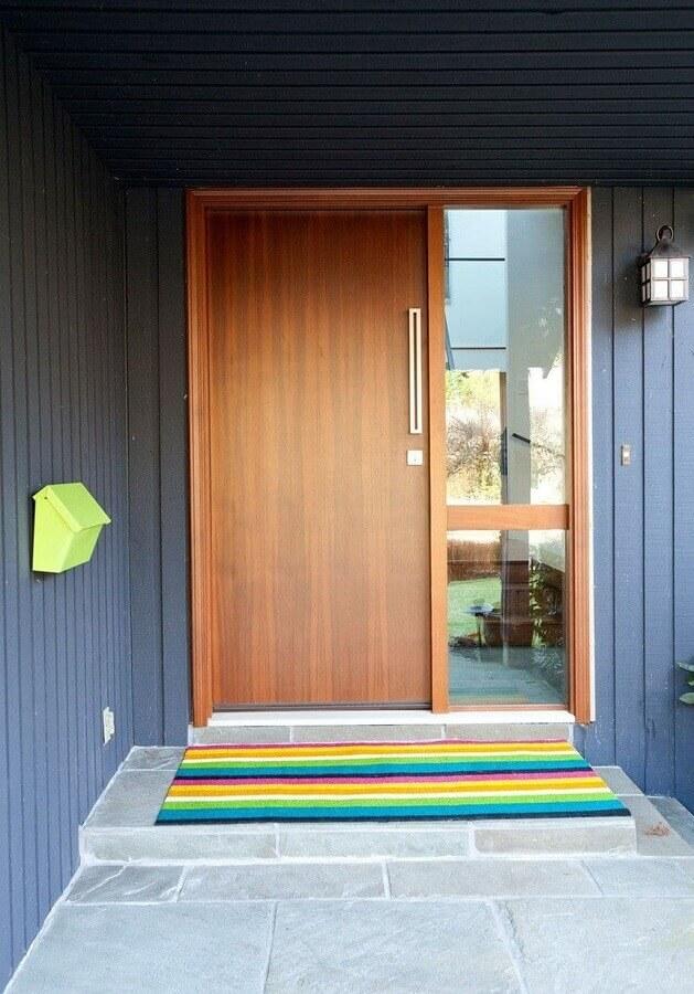 fachada com porta de madeira e tapete para porta de entrada com listras coloridas Foto House Plans