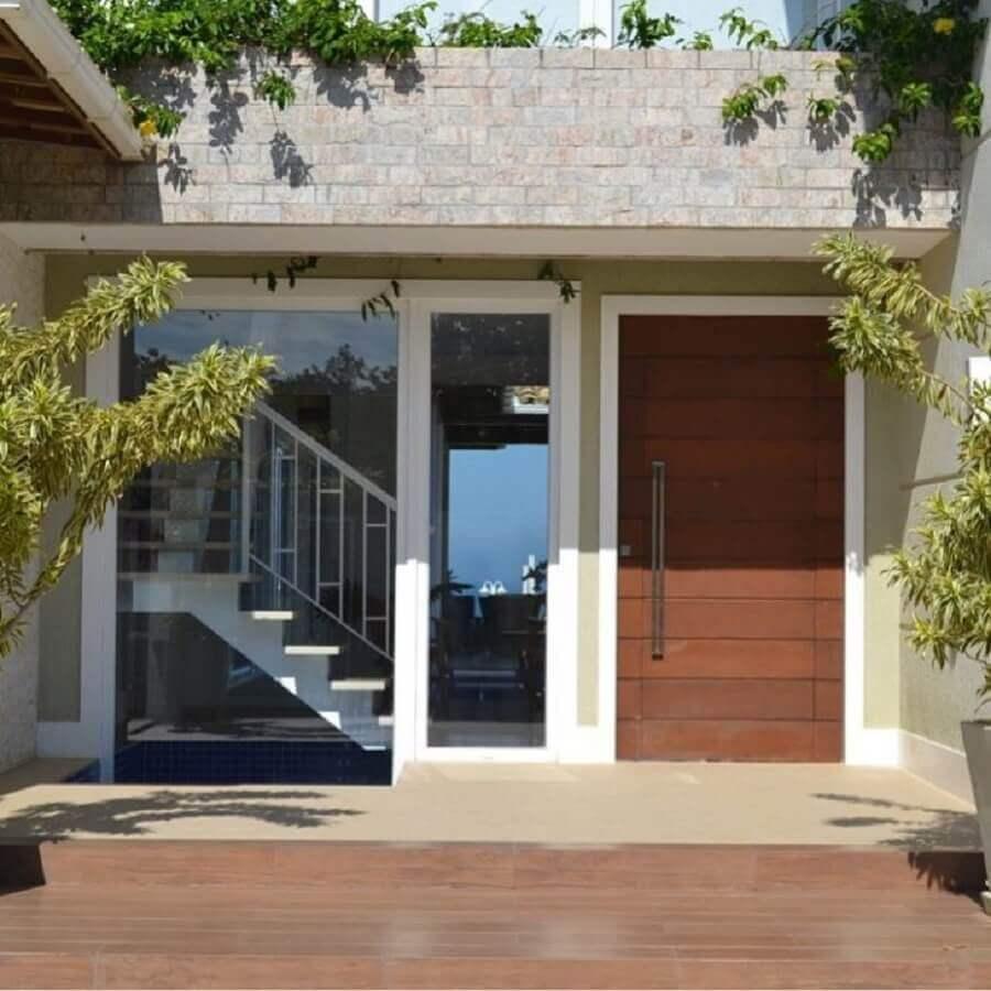 fachada de casa pequena com porta de entrada de madeira com detalhes na horizontal Foto Vivian Barros Arquiteta