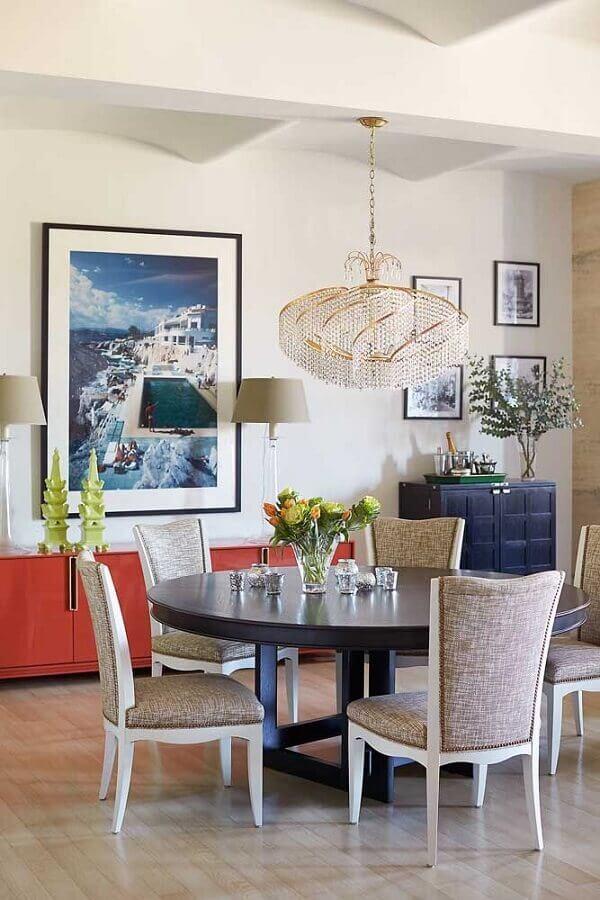 lustre de cristal redondo para decoração de sala de jantar com mesa redonda de madeira quadros na parede e aparador vermelho Foto HGTV