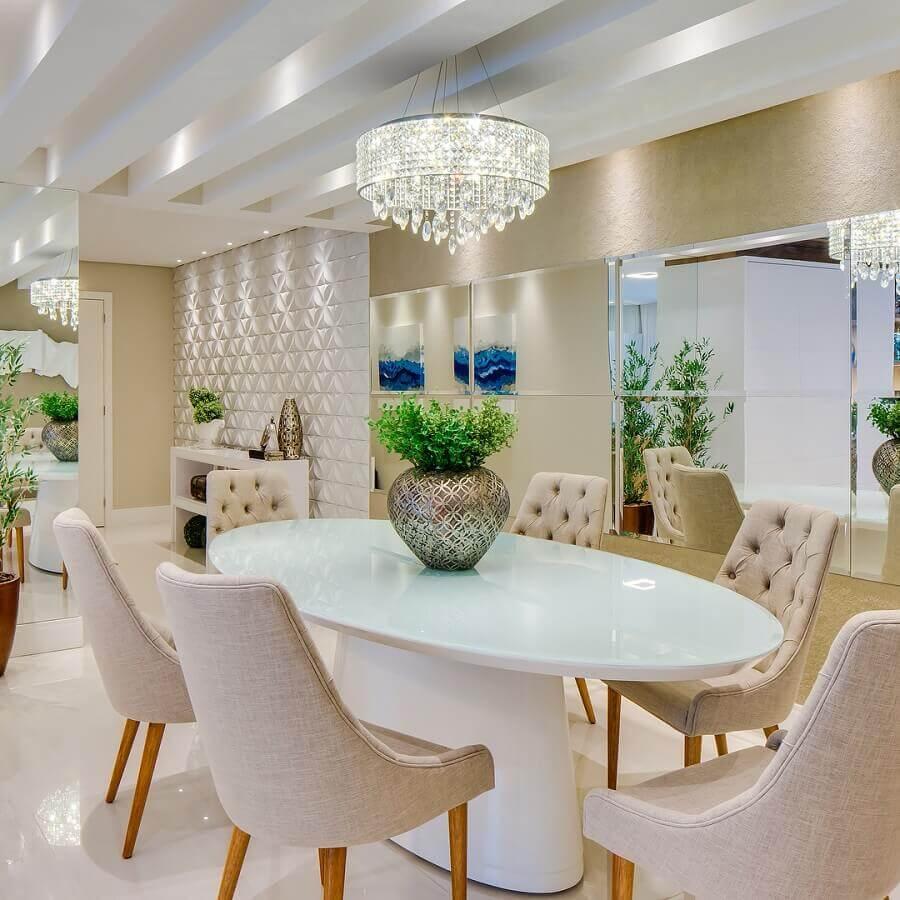 lustres de cristal para sala de jantar sofisticada decorada com mesa branca oval e cadeiras com acabamento capitonê Foto Janaina Marques e Jenny Fergotardo