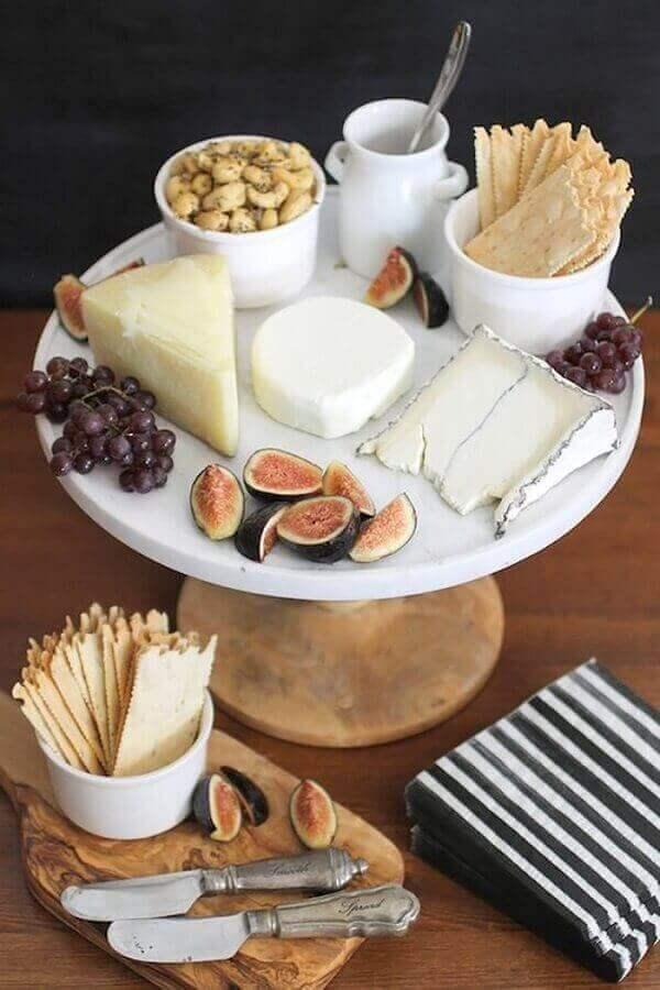 mesa de frios decorada com prato redondo branco e tábua de madeira pequena Foto L&M Home