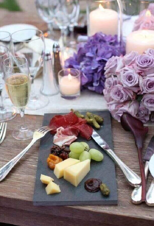 mesa de frios para casamento decorado com velas e arranjos de flores roxas Foto Pinosy