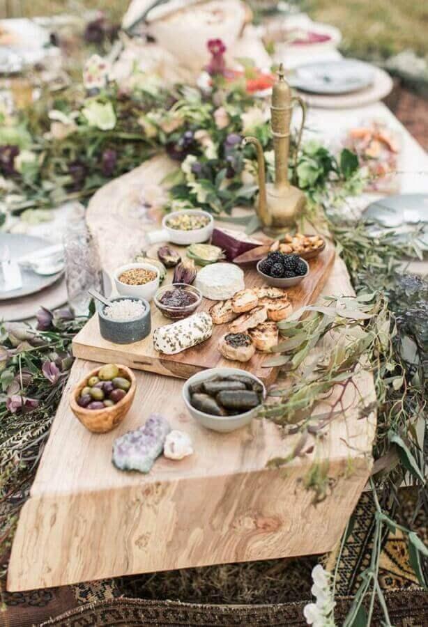mesa de frios para casamento rústico decorado com folhagens e tábuas de madeira Foto Assetproject