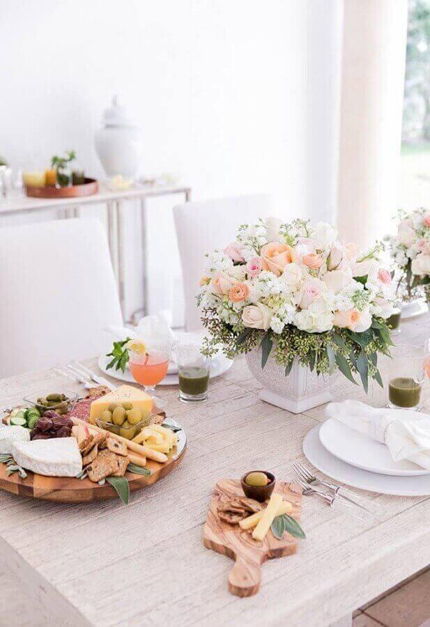 mesa de frios para festa com decoração delicada com arranjos de flores e tábuas de madeira Foto Pinterest