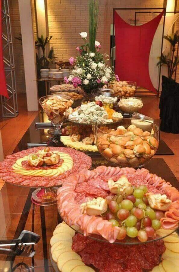 mesa de frios para festa decorada com arranjos de flores Foto Armonie Assessoria