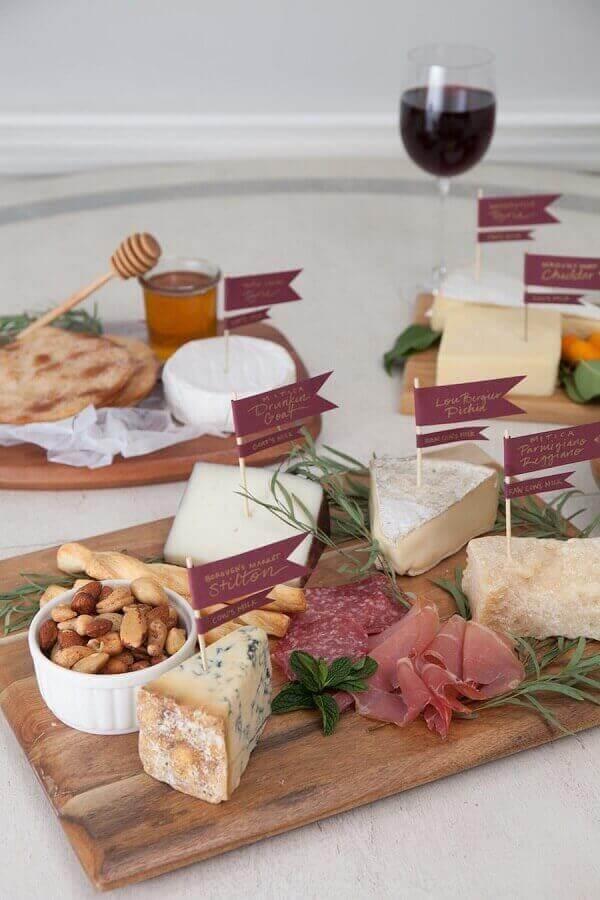 mesa de frios para festa decorada com plaquinhas com nomes dos queijos e pote de mel Foto Style Me Pretty