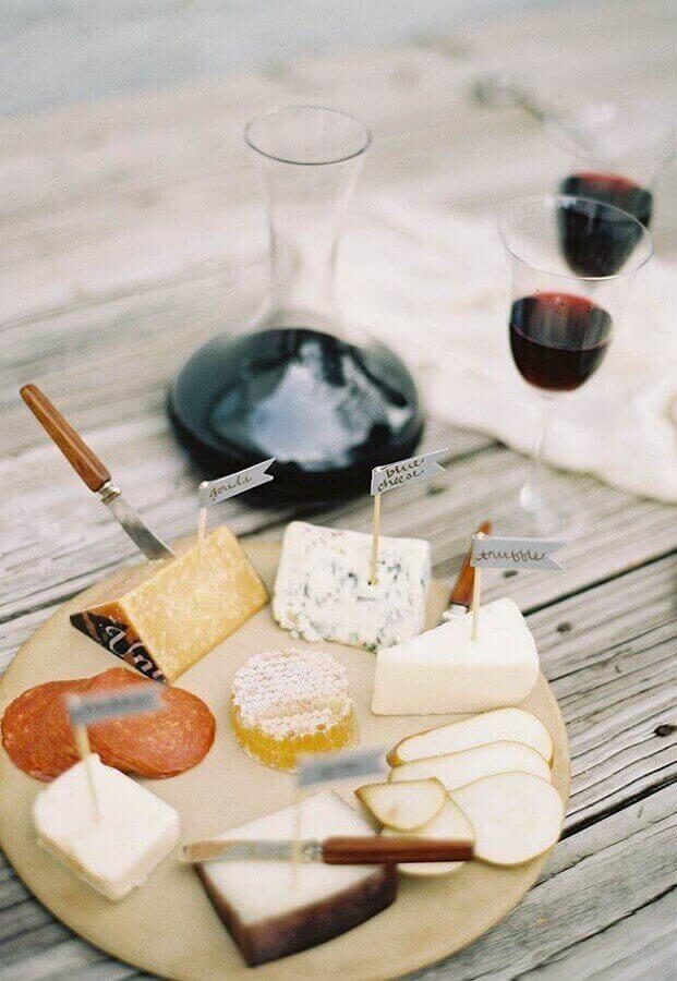 mesa de frios simples decorada com pequena tábua redonda e taças de vinho Foto Assetproject