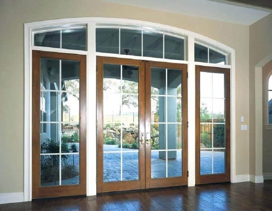 porta de entrada com duas folhas feita em madeira e vidro Foto TMC Enterprises