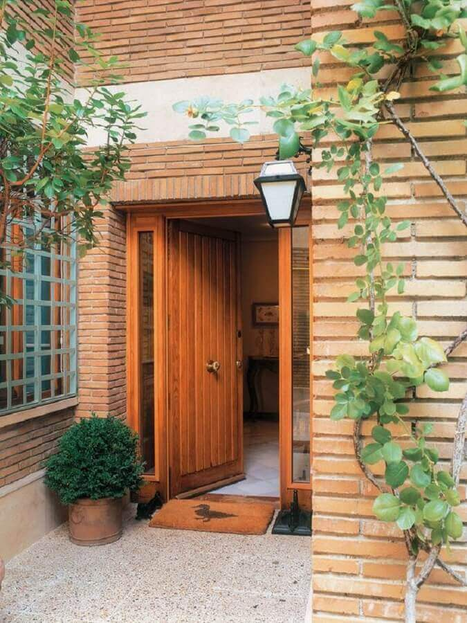 porta de entrada de madeira com fachada de tijolo a vista Foto Pinterest