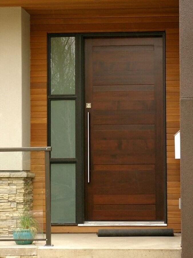 porta de entrada de madeira com puxador em metal e uma lateral com detalhe em vidro Foto Pinterest