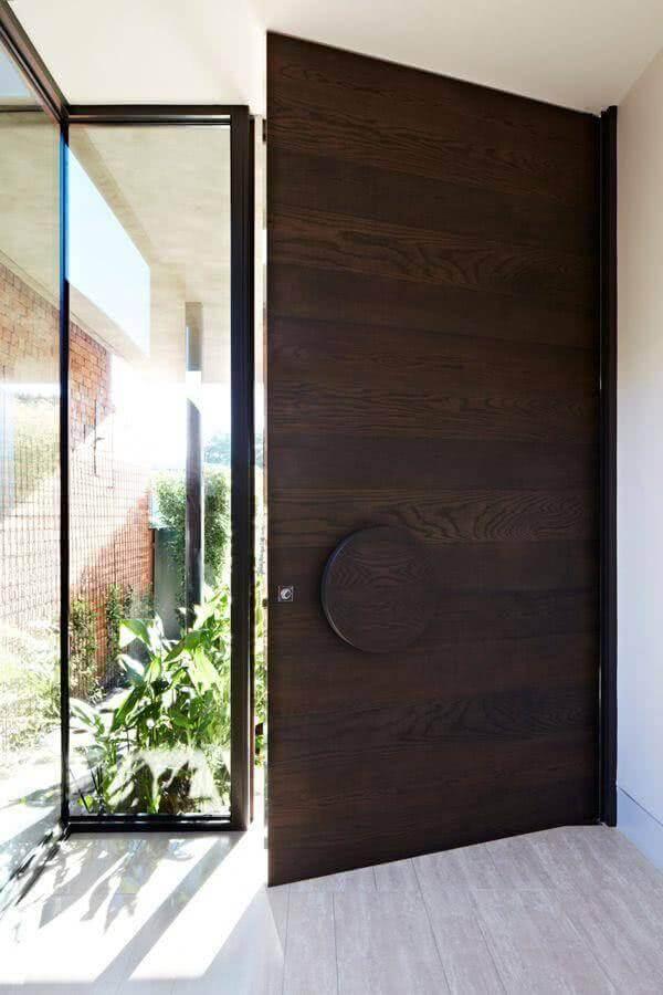 porta de entrada de madeira com puxador redondo grande de madeira e lateral de vidro Foto CafeLand
