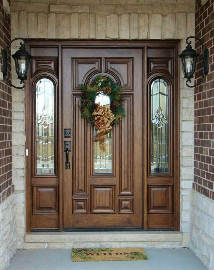 porta de entrada de madeira decorada com guirlanda natalina e capacho Foto AW Door