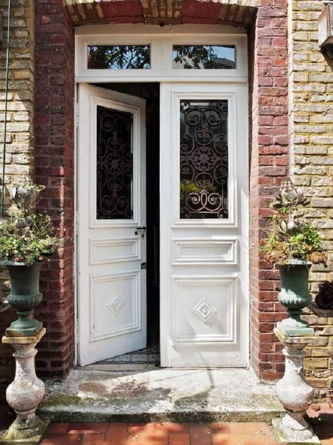 porta de entrada principal branca feita em madeira e vidro Foto Pinosy