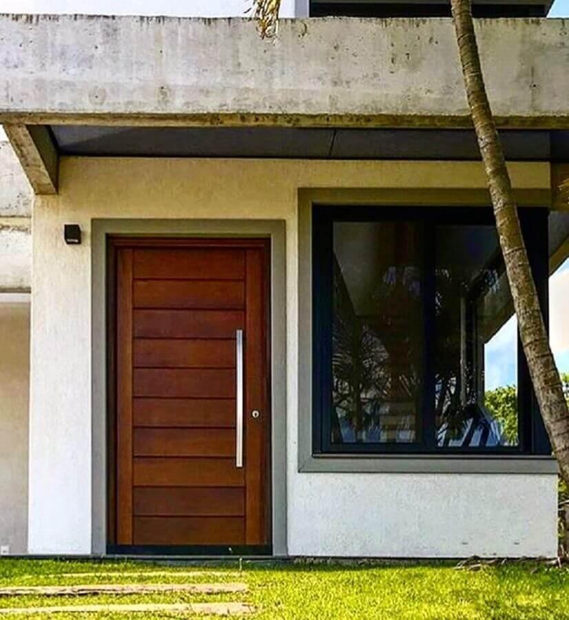 porta de entrada principal de madeira com detalhes na horizontal Foto Schramm Arquitetura e Engenharia