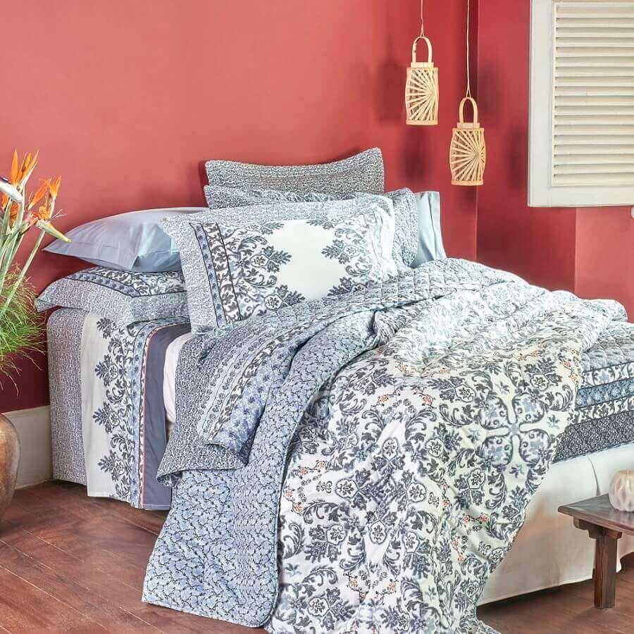 quarto decorado com parede goiaba e cama com muitos travesseiros e lençóis azuis
