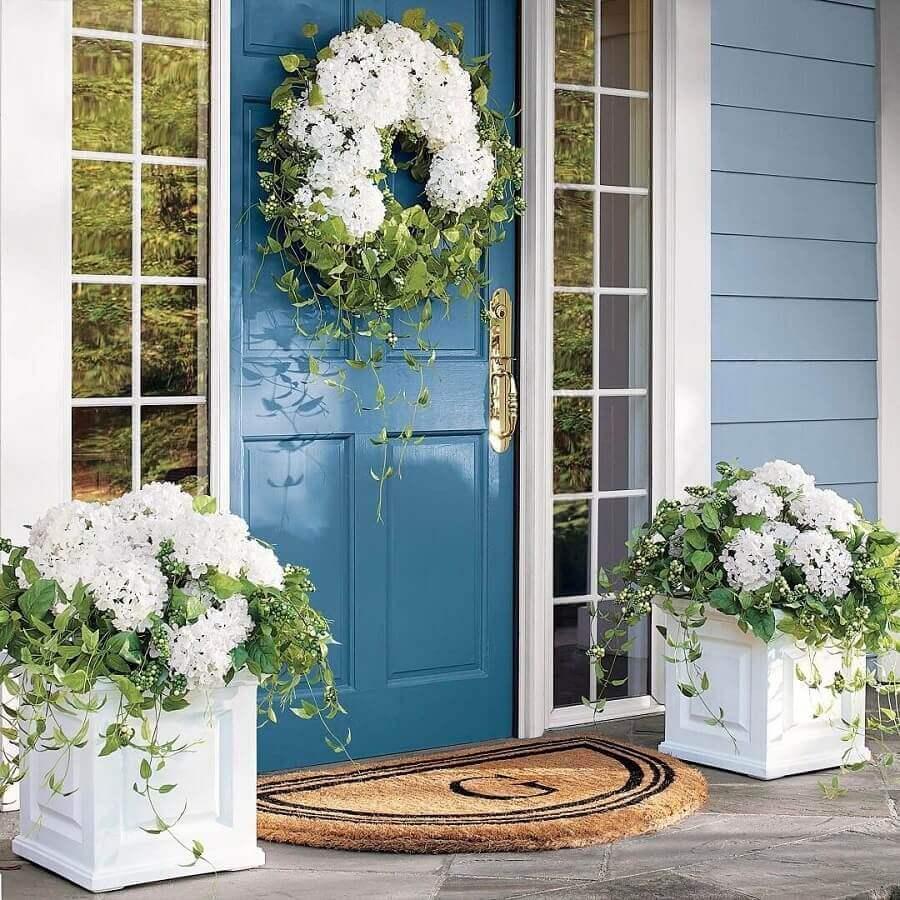tapete meia lua para porta de entrada azul decorada com guirlanda de flores brancas Foto Pinosy