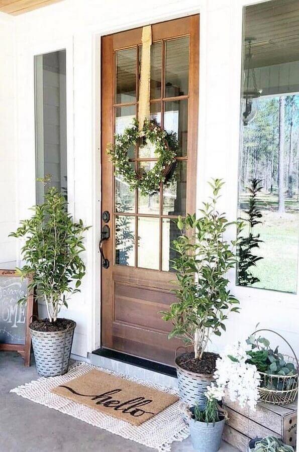 tapete para porta de entrada de madeira decorada com guirlanda Foto L'Essenziale