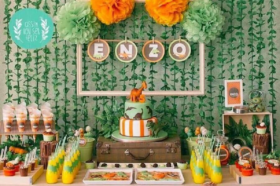 tema dinossauro para decoração de aniversário menino com painel de folhagens e bolo dois andares Foto Pinterest