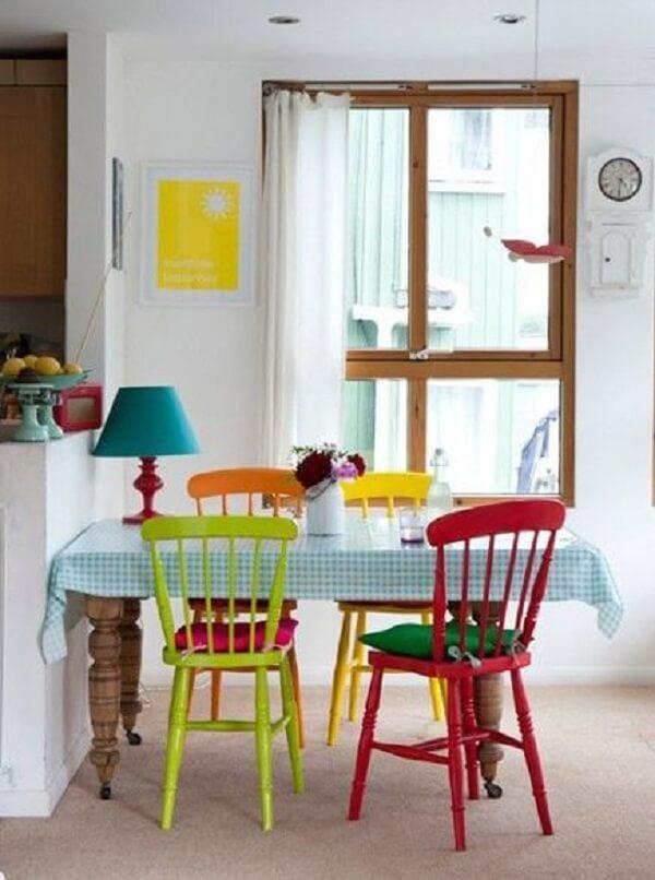 Decoração de sala simples e barata tem mesa branca com cadeiras coloridas
