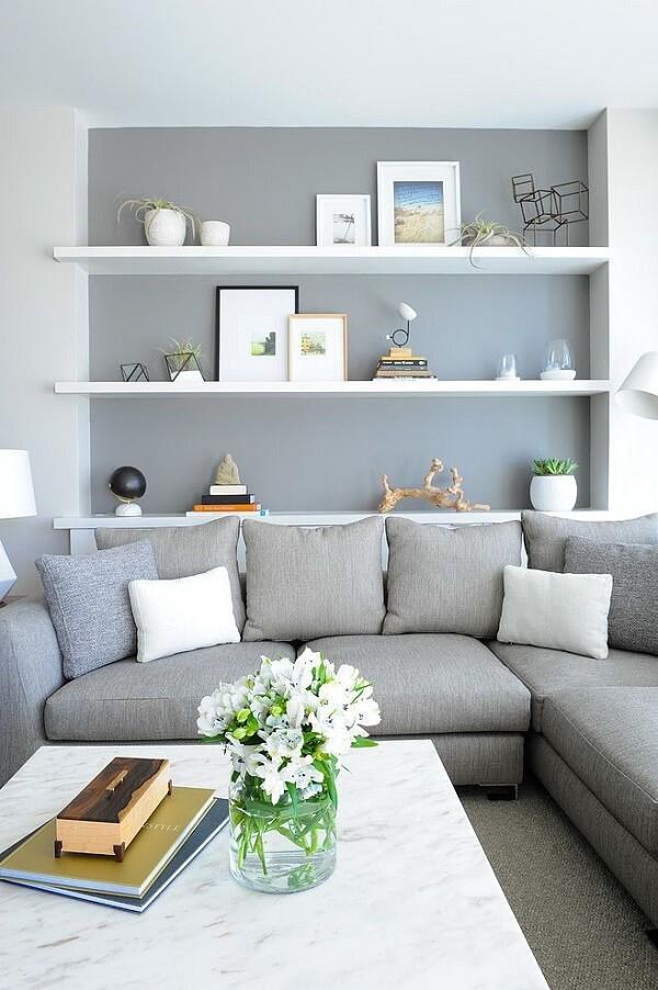 Decoração de sala simples e barata com parede cinza e prateleiras brancas