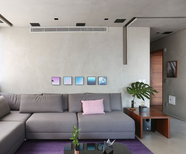 Roxo em tapete e sofá em L na cor cinza