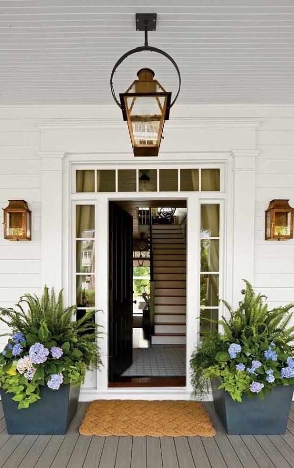 Vasos robustos com samambaias logo na entrada de casa