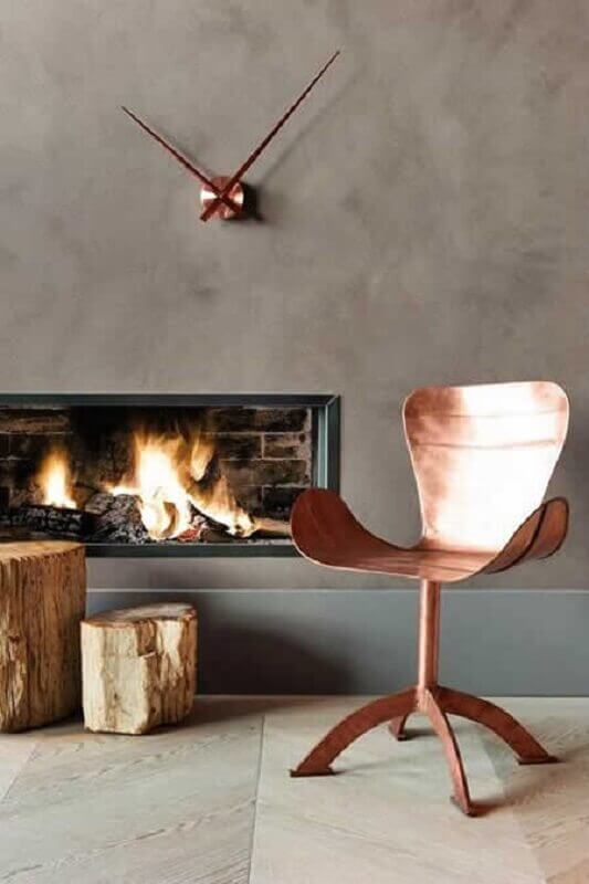 cadeira na cor cobre para decoração de sala com cimento queimado e lareira Foto Gavia Concept